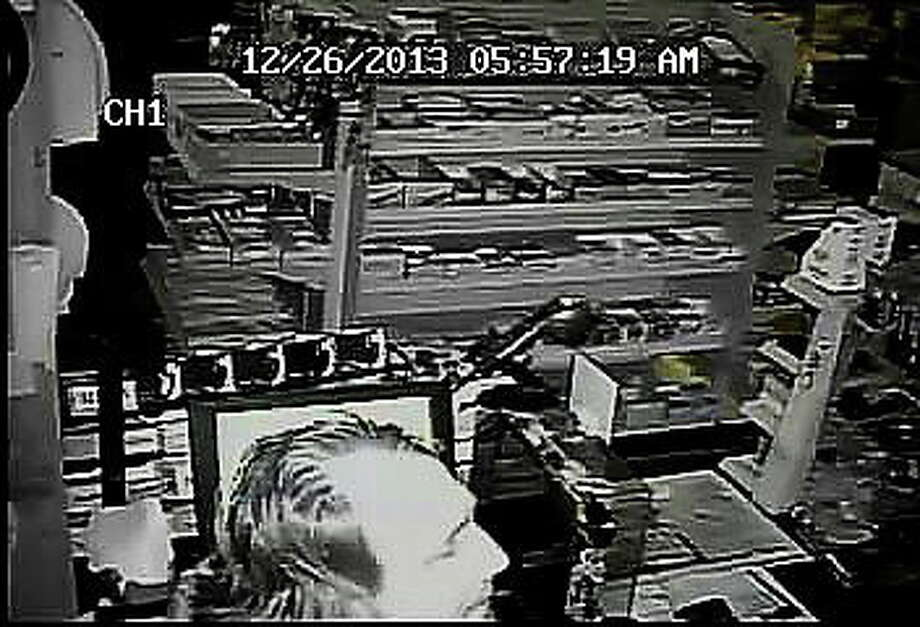 Photos from store surveillance system of the suspect police are searching for following burglary at North Madison Garage Convenience Store. Photo: Journal Register Co.