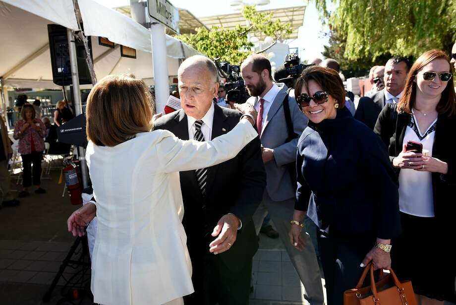 Gov. Jerry Brown gets a hug from House Minority Leader Nancy Pelosi as Rep. Anna Eshoo (second from right) and other dignitaries join them at the groundbreaking ceremony for Caltrain's electrification project at the Millbrae Station. Photo: Michael Short, Special To The Chronicle