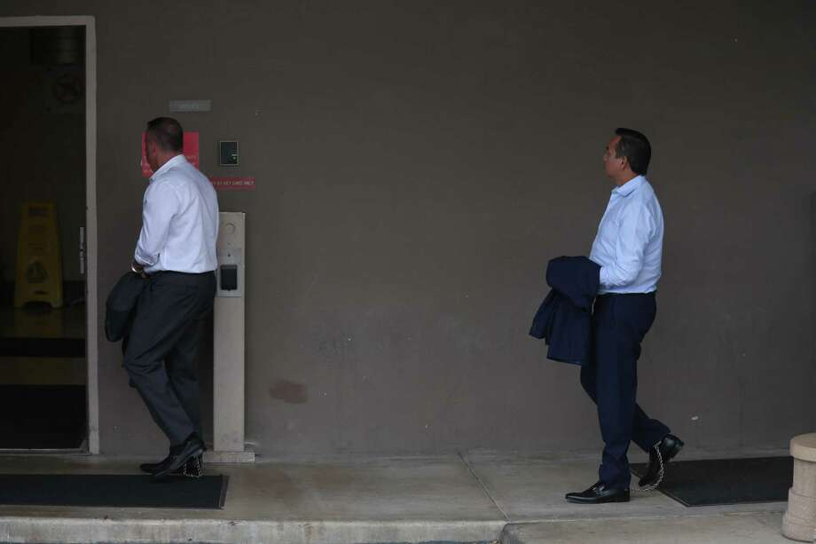 Stan Bates, left, is followed by State Sen. Carlos Uresti (D), right, as they are led by law enforcement into the federal courthouse May 17 following their arrests. They have been charged in connection with their involvement in FourWinds Logistics, a defunct oil-field services company. Photo: Jerry Lara /San Antonio Express-News / 2017 San Antonio Express-News
