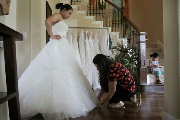 Monica Narvaez checks the bottom of Marcela Trejo's wedding dress during a fitting on Friday in Tomball. Trejo was able to get her dress for her July 29 wedding out of Alfred Angelo's store before it closed.