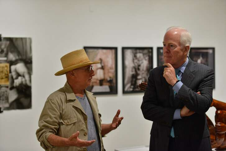 """Sen. John Cornyn talks with artist Cesar Martinez during a tour of the """"Icons and Symbols of the Borderland"""" exhibit Friday at Centro de Artes."""