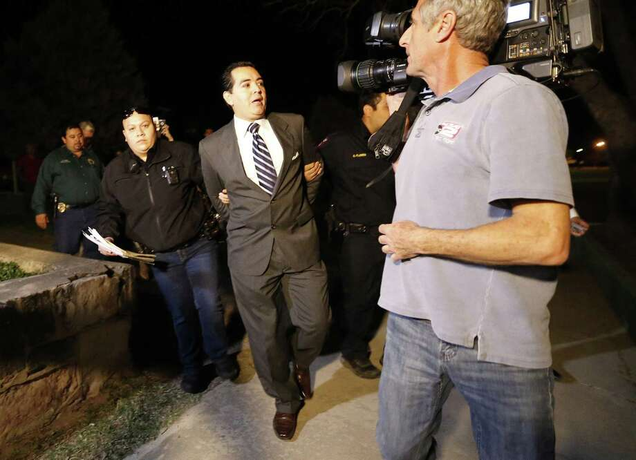 Crystal City Mayor Ricardo Lopez is taken away from city hall by police after a scuffle with citizens during a heated council meeting to suspend city manager James Jonas III and to force a recall election after Jonas and three city council members were faced federal corruption charges on Tuesday, Feb. 16, 2016. (Kin Man Hui/San Antonio Express-News) Photo: Kin Man Hui, Staff / San Antonio Express-News / ©2016 San Antonio Express-News