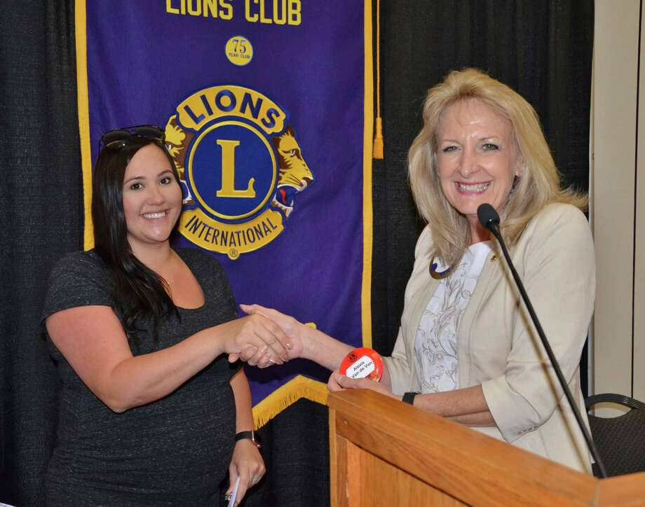Conroe Noon Lions Club President Helen Thornton, right, presents new member Alexis Van de Ven, left, her official blue member name badge after earning points by working on projects like the new member 'Pet Food Drive'. Photo: Submitted Photo