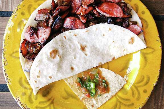 Barbecue-style brisket and sausage taco on a handmade flour tortilla from Taco Rey.