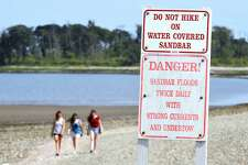 Signs posted at Silver Sands State Park in Milford warn of the danger of crossing the sandbar to Charles Island when it is covered with water on 7/21/2017.  Arnold Gold / Hearst Connecticut Media