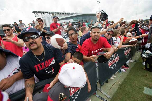 Houston Texans fans line a fence seeking autographs during Texans training camp at Houston Methodist Training Center on Sunday, July 31, 2016, in Houston. ( Brett Coomer / Houston Chronicle )
