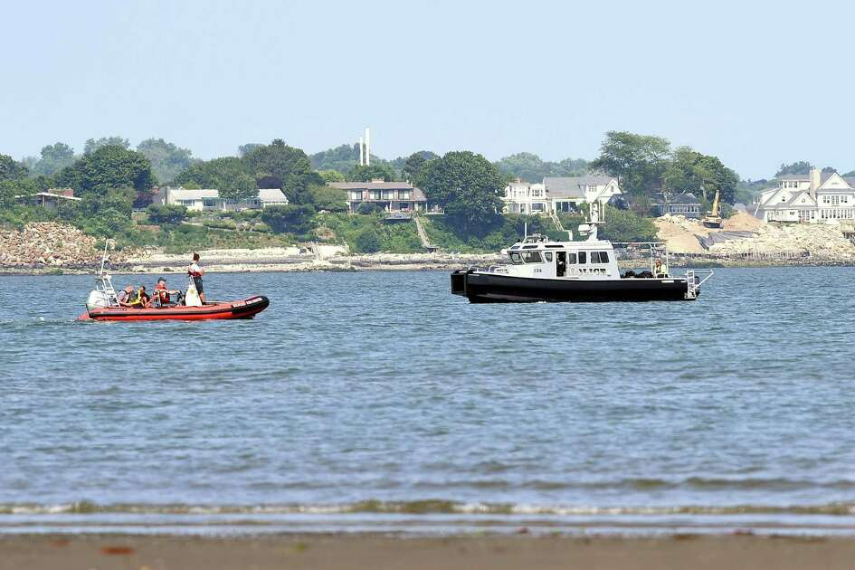 Milford emergency personnel search for a man who was swept off of a sandbar into the water while walking out to Charles Island at Silver Sands State Park in Milford on Friday.