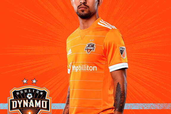 "Houston Dynamo A.J. DeLaGarza unveils the new 2017 home kit. Space City Blue returns to the home kit for the first time since 2010, with blue horizontal pinstripes accenting the club's traditional orange shirt. The rest of the kit features white shorts with Space City Blue accent stripes, leaving behind the traditional orange stripes, and orange socks with Space City Blue pinstripes to match the jersey.  The club motto, ""FOREVER ORANGE,"" is on the back of the jersey beneath the collar, and the front of the jersey bears the club crest with two silver stars representing the club's back-to-back MLS Cup wins in 2006 and 2007."