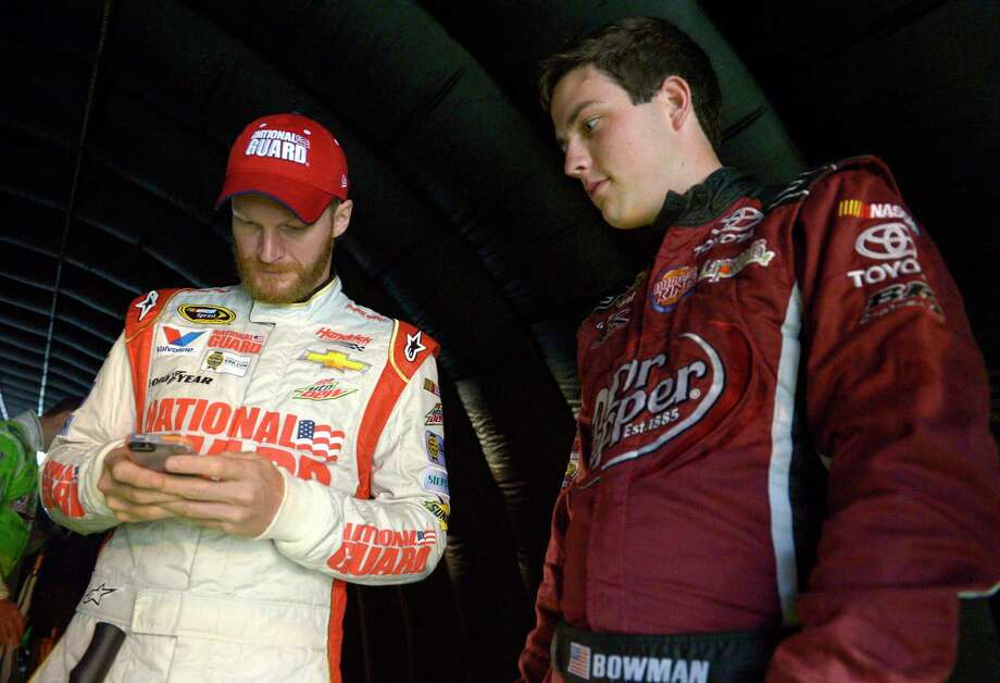 FILE - In this July 5, 2014, file photo, Alex Bowman, right, watches as Dale Earnhardt Jr. sends out a tweet while waiting under a tunnel for driver introductions to begin before a NASCAR Sprint Cup Series auto race at the Daytona International Speedway, in Daytona Beach, Fla. Dale Earnhardt Jr. got the replacement he wanted. Alex Bowman got his dream job. Hendrick Motorsports announced Thursday, July 20, 2017, that the 24-year-old Bowman will replace one of the series' biggest stars in the No. 88 car next season after Earnhardt retires.(AP Photo/Phelan M. Ebenhack, File) Photo: Phelan M. Ebenhack, FRE / FR121174 AP