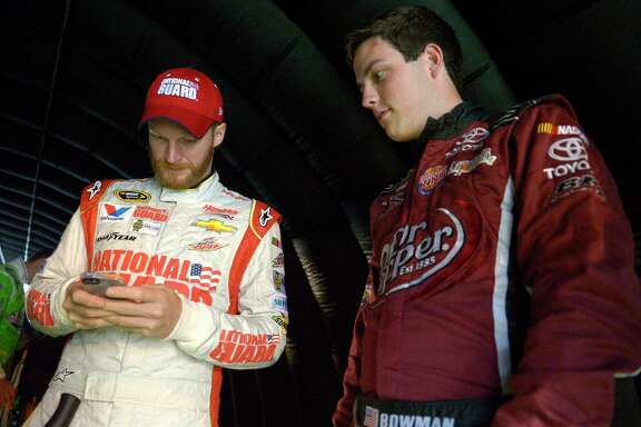 FILE - In this July 5, 2014, file photo, Alex Bowman, right, watches as Dale Earnhardt Jr. sends out a tweet while waiting under a tunnel for driver introductions to begin before a NASCAR Sprint Cup Series auto race at the Daytona International Speedway, in Daytona Beach, Fla. Dale Earnhardt Jr. got the replacement he wanted. Alex Bowman got his dream job. Hendrick Motorsports announced Thursday, July 20, 2017, that the 24-year-old Bowman will replace one of the series' biggest stars in the No. 88 car next season after Earnhardt retires.(AP Photo/Phelan M. Ebenhack, File)