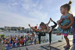Sierra Wolfenden, 2, of Stamford, at far right, follows along as she, along with 50 yoga enthusiasts participate in the 5th annual Yoga Jam 2017 at Harbor Point Boardwalk on Friday, July 21, 2017 in Stamford, Connecticut. The event was co-sponsored by lululemon Greenwich and Exhale Spa.