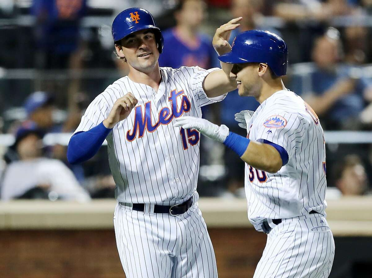NEW YORK, NY - JULY 21: Matt Reynolds #15 of the New York Mets congratulates teammate Michael Conforto #30 after Conforto hit a home run to score them both in the seventh inning against the Oakland Athletics on July 21, 2017 at Citi Field in the Flushing neighborhood of the Queens borough of New York City. (Photo by Elsa/Getty Images)