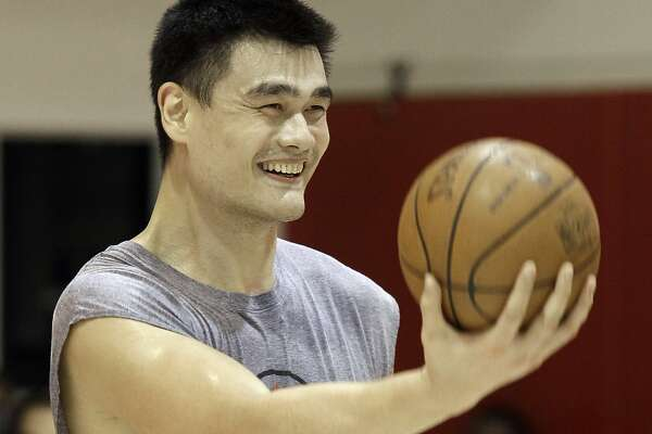 Houston Rockets center Yao Ming, of China, smiles as the holds out a basketball for a teammate during a workout Tuesday, Aug. 24, 2010 in Houston. Yao underwent a medical evaluation Monday which revealed the hairline fracture in his surgically repaired left foot has fully healed. He has been cleared to take part in normal basketball activities. (AP Photo/David J. Phillip)