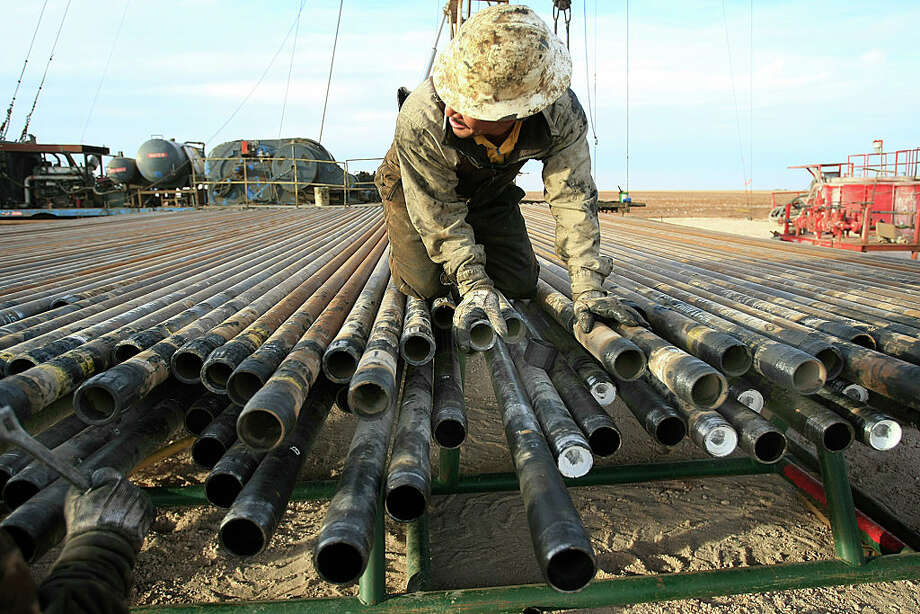 An oil rigger prepares pipes at a Schlumberger field in Midland. The company says its onshore North American revenues jumped 42 percent from the first quarter. / 2015 Los Angeles Times