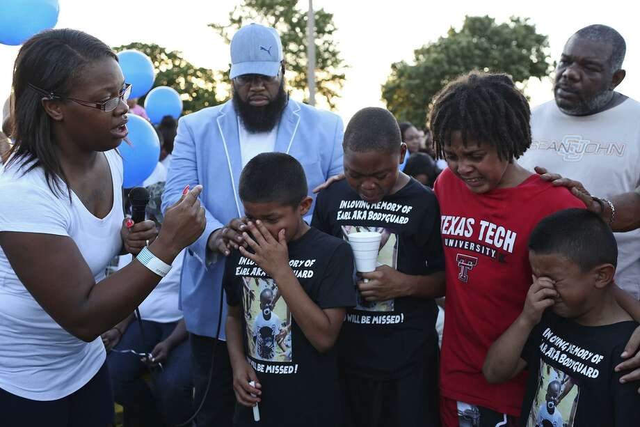 Cyntwanisha Whitley encourages football teammates of her son, 4-year-old De'Earlvion Whitley, including Romeo Perez (from left), 11, Albert Goodloe, 11, Coner Hall, 11, and Angel Perez, 7, during a Friday vigil for De'Earlvion at Copernicus Park. Standing with the boys are Pastor Royce Sullivan (left) and minister Darrell Boyce. Photo: Lisa Krantz /San Antonio Express-news / SAN ANTONIO EXPRESS-NEWS