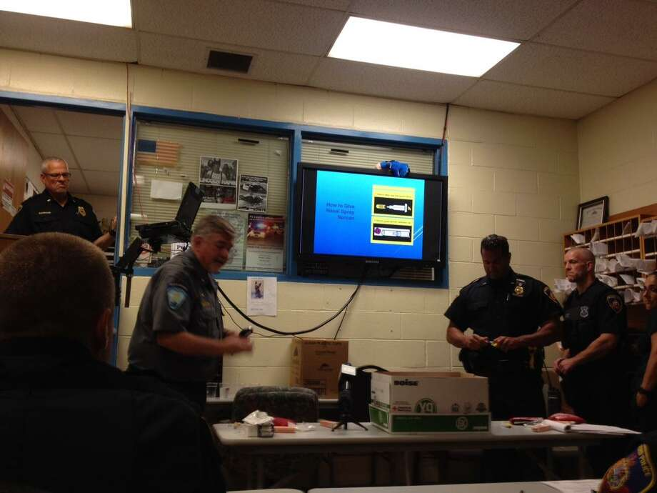 Deputy Chief of Training for Stamford Emergency Medical Services, Joe Larcheveque, and police Lt. Diedrich Hohn (center) talk to police officers about how to use Narcan if they run into an overdose victim on the job at Stamford police headquarters Wednesday afternoon. Photo: John Nickerson / Staff