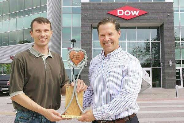 Josh Stevens, a local Bike to Work Weekorganizer, presents a trophy to Mike Witt, Dow Chemical director of health and environmental research, who received the trophy on behalf of Dow Chemical.
