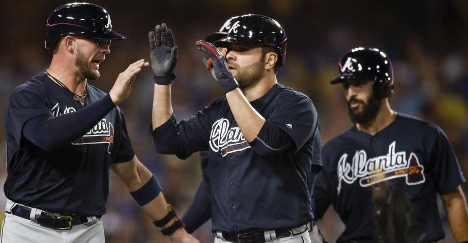 Atlanta Braves' Jaime Garcia, center, celebrates with Tyler Flowers, left, after hitting a grand slam off Los Angeles Dodgers starting pitcher Alex Wood, as Sean Rodriguez trails during the fifth inning of a baseball game in Los Angeles, Friday, July 21, 2017. (AP Photo/Kelvin Kuo) Photo: Kelvin Kuo/Associated Press