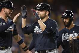 CORRECTS PLAYER AT LEFT TO TYLER FLOWERS, INSTEAD OF ENDER INCIARTE - Atlanta Braves' Jaime Garcia, center, celebrates with Tyler Flowers, left, after hitting a grand slam off Los Angeles Dodgers starting pitcher Alex Wood, as Sean Rodriguez trails during the fifth inning of a baseball game in Los Angeles, Friday, July 21, 2017. (AP Photo/Kelvin Kuo)