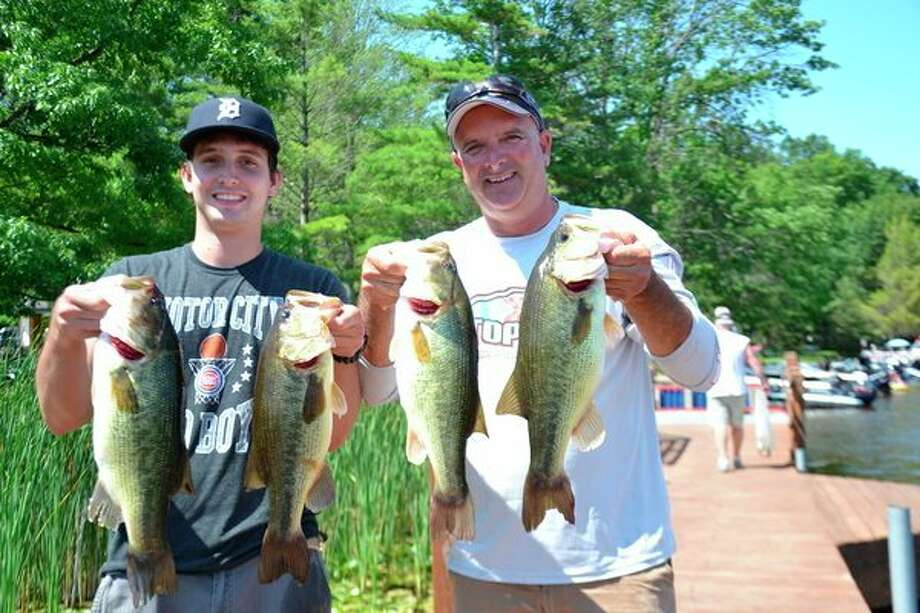 Tanner (left) and his father Kevin Vida pose with four of the five fish they caught to win last Saturday's Sanford Lake Open tournament, conducted by the Sanford Lake Bass Club. The catch totaled 17.54 pounds, including the tourney's single heaviest bass, a 4.22-pounder. (Photo for the Daily News by Steve Griffin)