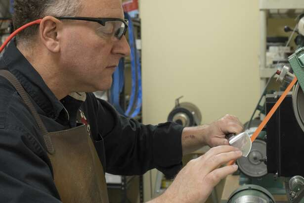 Shop owner Richard Steinberg sharpens a customer's knife in the workshop area at Bear Claw on June 28.