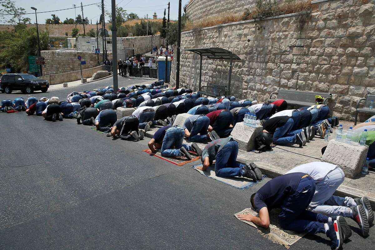 Palestinian Muslim worshippers pray outside Lions' Gate, a main entrance to the Al-Aqsa mosque compound in Jerusalem's Old City, on July 22, 2017, in protest against new Israeli security measures implemented at the holy site following an attack that killed two Israeli policemen the previous week. Stabbings and clashes that left six people dead raised fears of further Israeli-Palestinian violence as tensions mount over new security measures at the highly sensitive Jerusalem holy site. / AFP PHOTO / AHMAD GHARABLIAHMAD GHARABLI/AFP/Getty Images