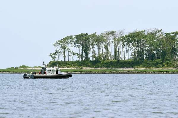 Emergency personnel search for a man who was swept off of a sandbar into the water while walking out to Charles Island at Silver Sands State Park in Milford, Conn. on Friday, July 21, 2017. He was still missing as of Saturday morning.