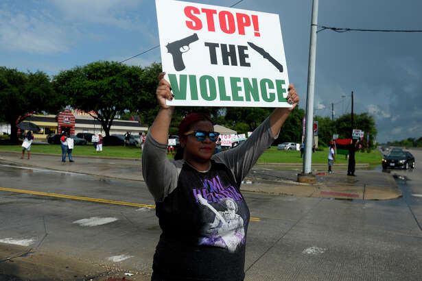 "Shena Stewart holds a sign during a ""Stop the Violence"" rally at the corner of Washington Boulevard and Martin Luther King Jr. Parkway on Saturday. The rally was organized in light of recent murders and violent crimes.  Photo taken Saturday 7/22/17 Ryan Pelham/The Enterprise"