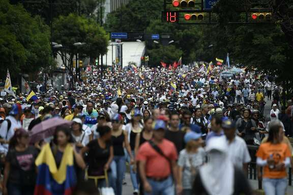 Opposition activists take part in a march towards the Supreme Court of Justice (TSJ) in Caracas in an offensive against President Maduro and his call for Constituent Assembly in Caracas on July 22, 2017. The Legislative power, controlled by the opposition, appointed Friday a parallel supreme court in a public session claiming the TSJ judges had been illegally appointed by the parliaments former pro-government majority. / AFP PHOTO / JUAN BARRETOJUAN BARRETO/AFP/Getty Images