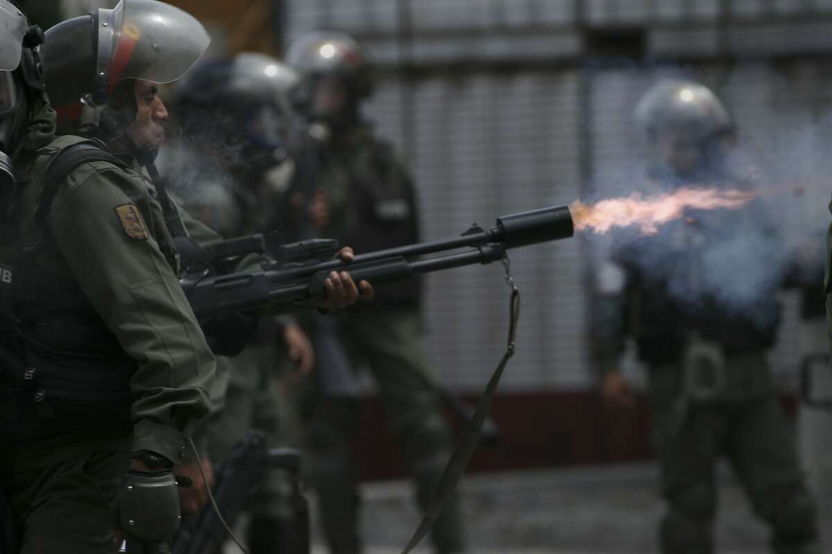 A Bolivarian National Guard officer fires tear gas canister aimed at anti-government protesters marching to the Supreme Court to support new magistrates named to the government-dominated Supreme Court by opposition-led led National Assembly, in Caracas, Venezuela, Saturday, July 22, 2017. (AP Photo/Fernando Llano)