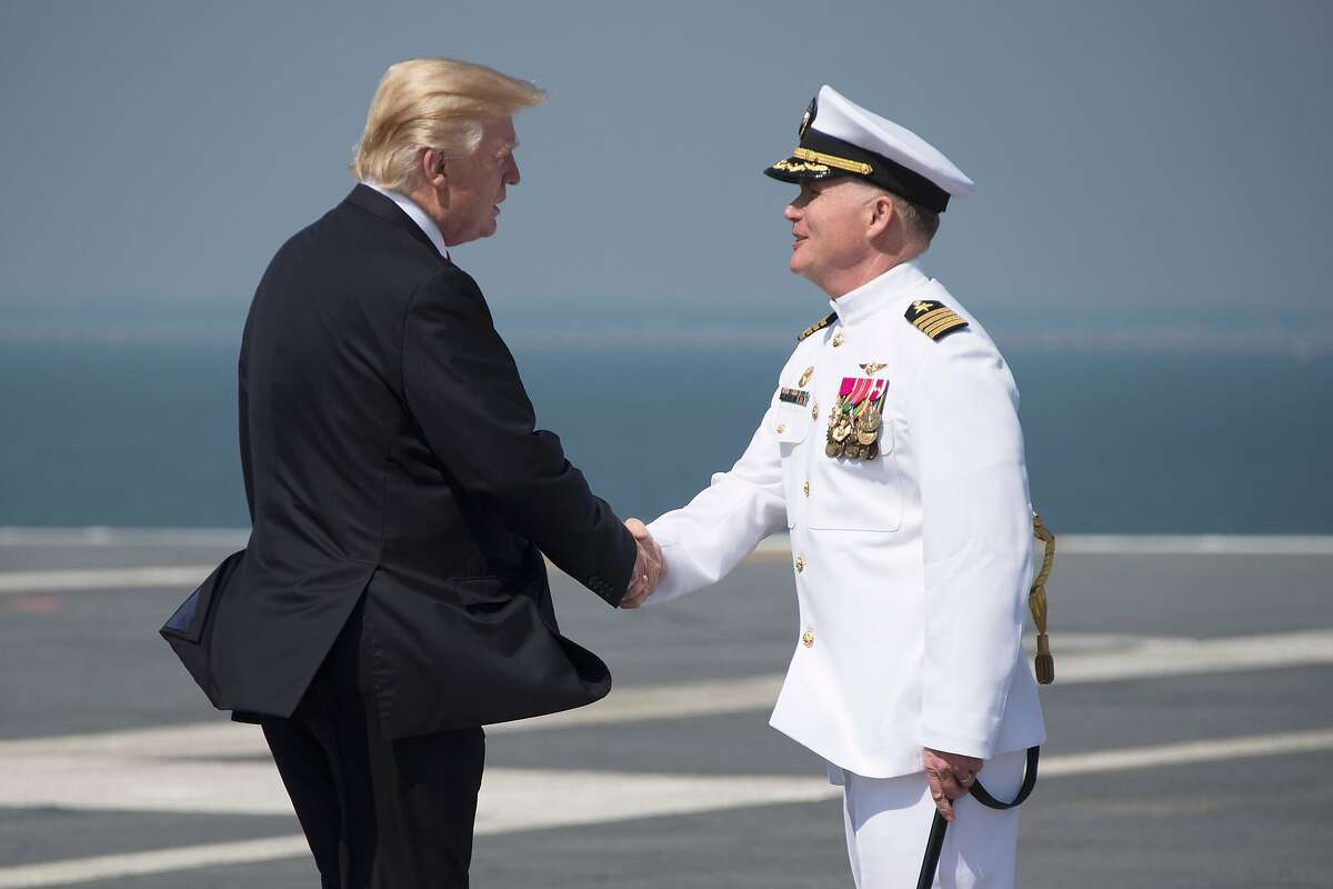 US President Donald Trump (L) is welcomed by USS Gerald R. Ford's Captain Rick McCormack (R) on the flight deck in Norfolk, Virginia, on July 22, 2017. / AFP PHOTO / JIM WATSONJIM WATSON/AFP/Getty Images