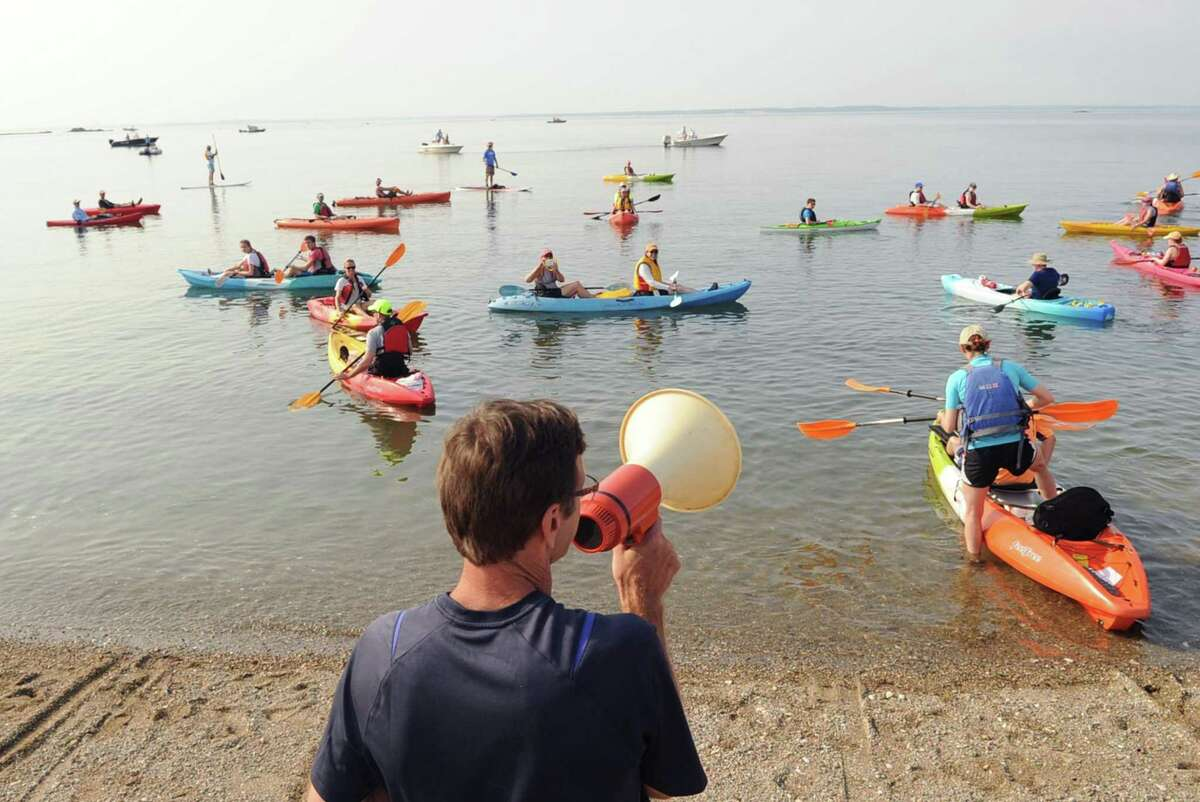 Bob Mazzone, center, vice president of SoundWaters, uses a megaphone for the official start of the SoundWaters Flotilla Fundraising Event to protect Long Island Sound, a kayak and paddle board event that started from Cove Island Park in Stamford, Conn., Saturday morning, July 22, 2017. The paddlers finished their 4-mile voyage of Long Island Sound on the west side of Stamford at Boccuzzi Park and celebrated with a beach party.