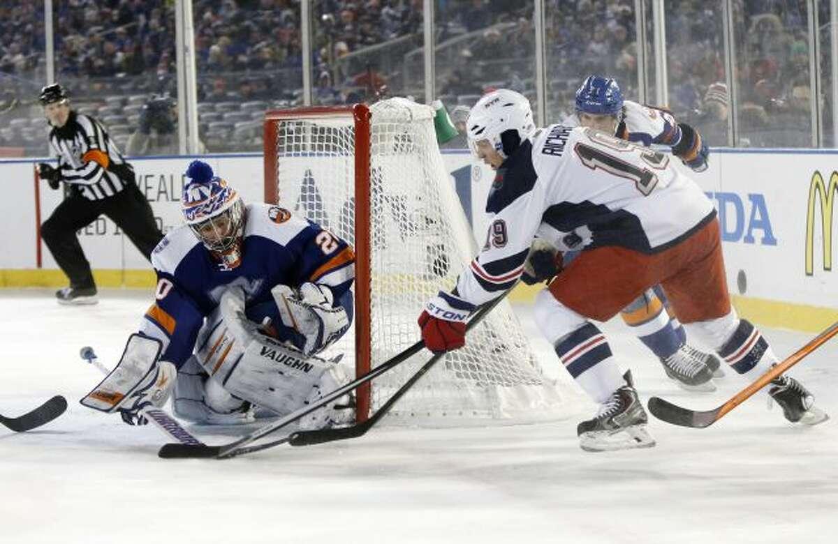 New York Islanders goalie Evgeni Nabokov (20) blocks a shot by New York Rangers center Brad Richards (19) in the second period of an outdoor NHL hockey game at Yankee Stadium in New York, Wednesday, Jan. 29, 2014. (AP Photo/Kathy Willens)