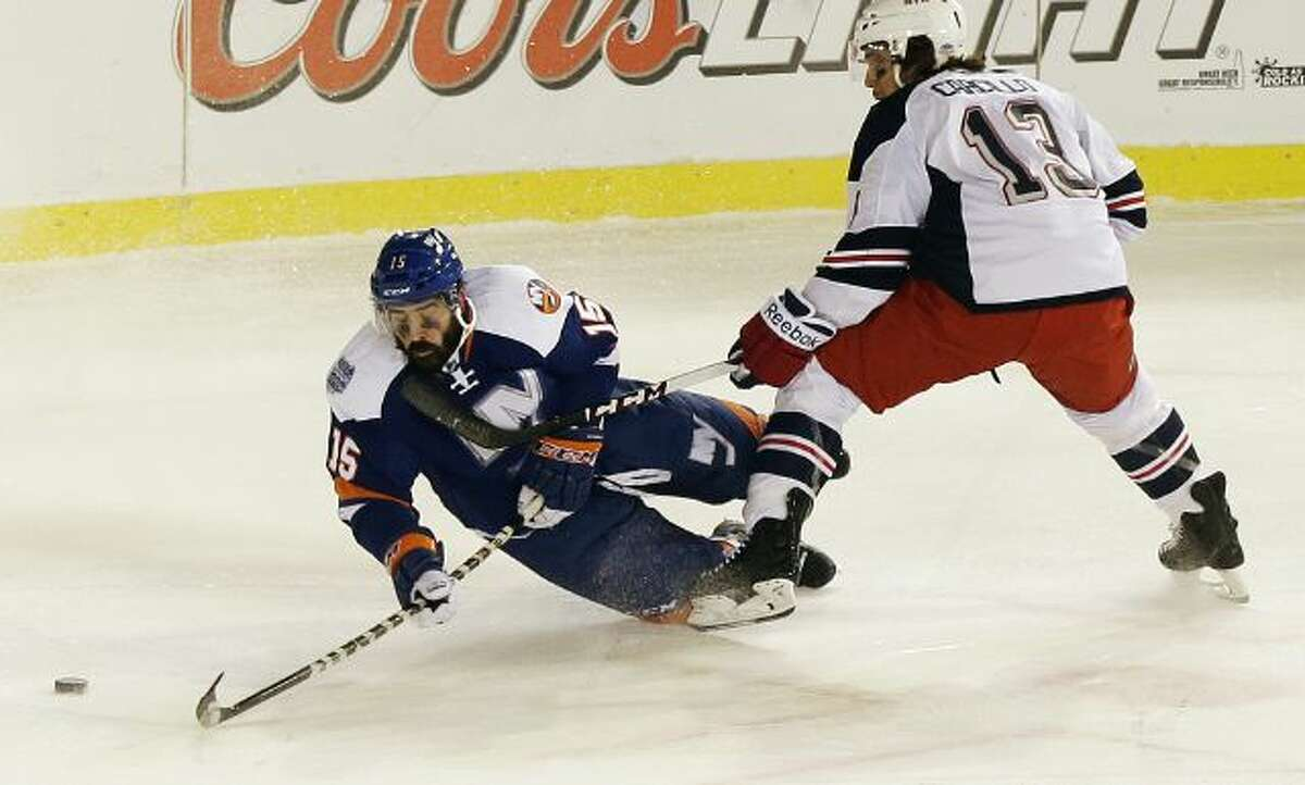 New York Islanders' Cal Clutterbuck (15) and New York Rangers' Daniel Carcillo (13) fight for control of the puck during the second period of an outdoor NHL hockey game Wednesday, Jan. 29, 2014, at Yankee Stadium in New York. (AP Photo/Frank Franklin II)