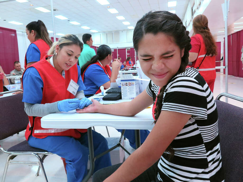 In this file photo, Luvia Trevino, 12, reacts as she gets her blood glucose checked by Ashley Gonzalez Monday at the LISD Performing Arts Center during Operation Lone Star. Photo: Cuate Santos/Laredo Morning Times