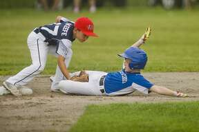 Fraternal Northwest's Hamper O'Keefe tags out a Gladwin opponent during their game on Saturday, July 22, 2017 in Mt. Pleasant.