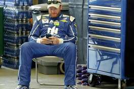 Race driver driver Dale Earnhardt Jr. looks at his phone before a practice session for the NASCAR auto race at Indianapolis Motor Speedway, in Indianapolis Saturday, July 22, 2017. (AP Photo/Darron Cummings)