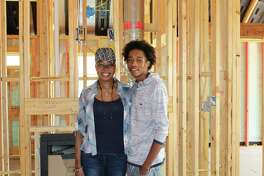 "U.S. Army SFC Demitra Jarrett and her son Trey stand in their new home under construction now in Woodforest. The home, being built by Coventry Homes, will be given to Jarrett mortgage-free through the Operation FINALLY HOME program. Last week, supporters wrote ""Notes of Love"" on the studs, concrete and other surfaces."
