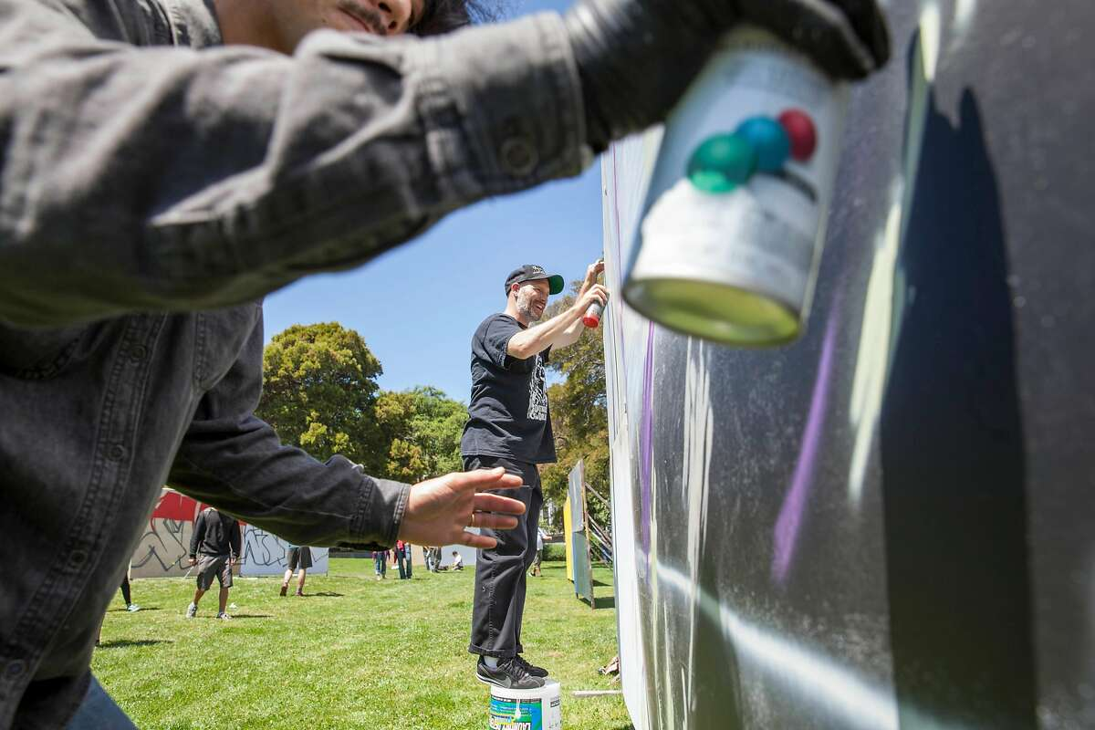 Matthew Bajda (rear) and Naomi Onodera, paint on their wall during the annual Urban Youth Arts Graffiti Festival at Precita Park in San Francisco on July 22, 2017. (Peter DaSilva/Special to The Chronicle)