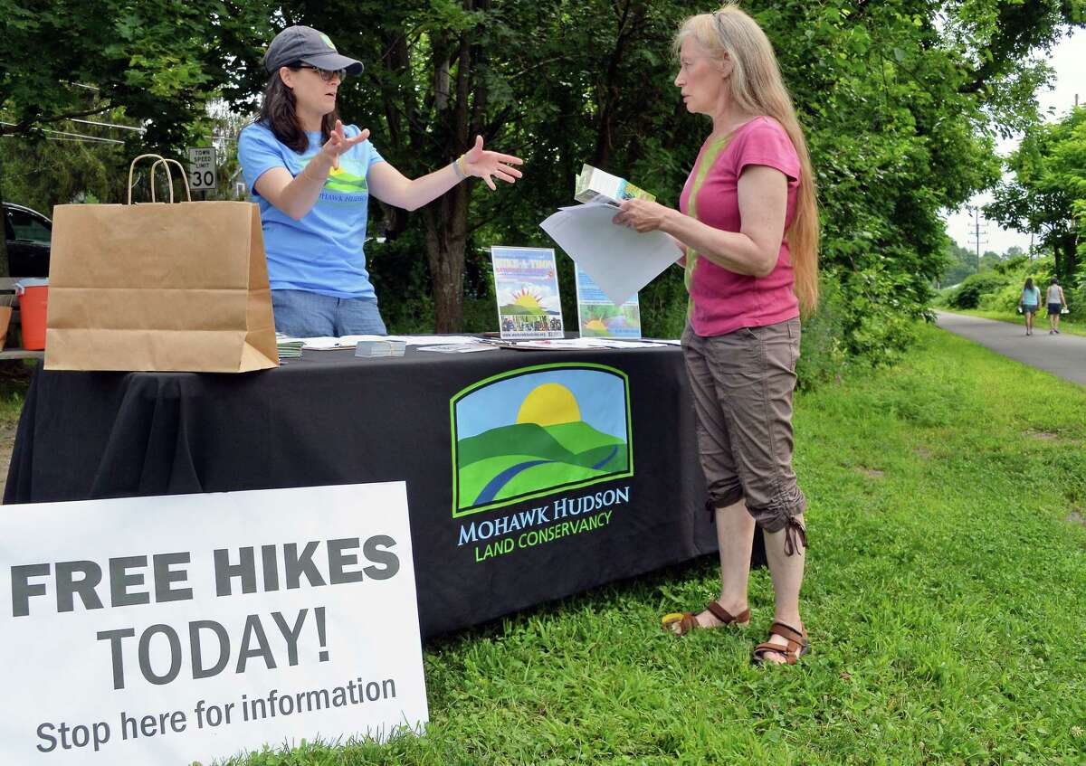 Mohawk Hudson Land Conservancy volunteer Donna Liquori, left, signs in hiker Susan Wolfe of New Scotland for a nature and history hike along the Albany County Helderberg-Hudson Rail Trail Saturday July 22, 2017 in Delmar, NY. (John Carl D'Annibale / Times Union)