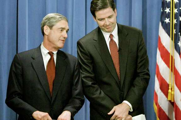 Then-FBI Director Robert Mueller, left, confers with then-Deputy U.S. Attorney General James Comey before announcing charges against Enron executive Jeffrey Skilling in 2004.
