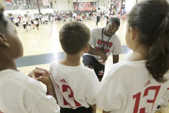 Coach Stephen Woods talks to his team about passing before scrimmaging during James Harden Basketball Procamp on Saturday, July 22, 2017, in the Woodlands. ( Elizabeth Conley / Houston Chronicle )