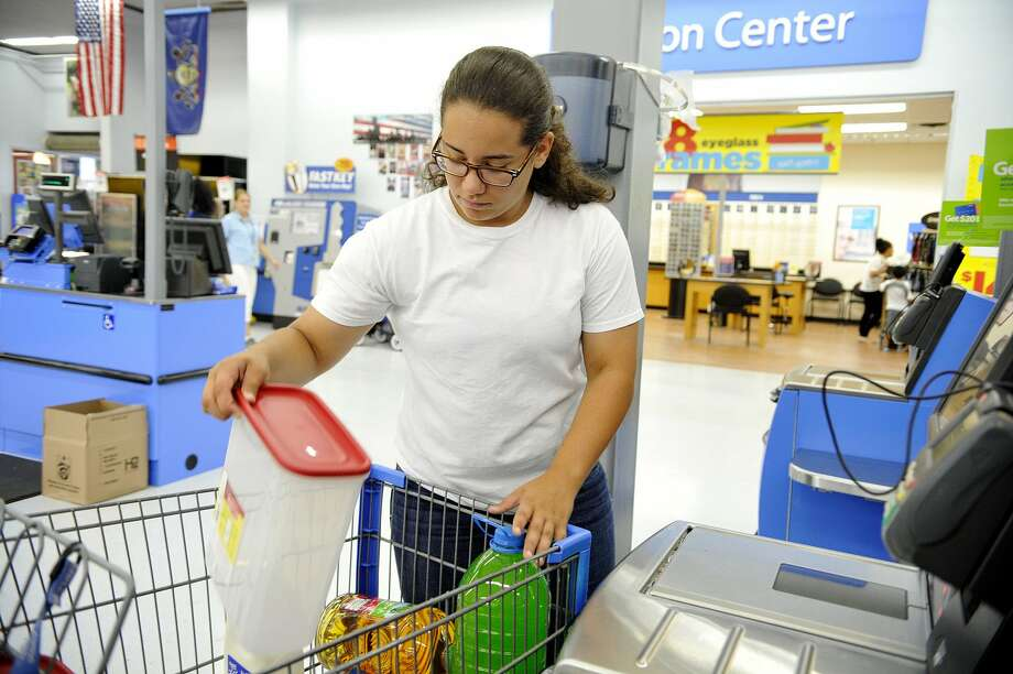 Kyristen Daniels, 14 of York, removes items from her cart to scan at a self-checkout station at Walmart on Wednesday, July 10, 2013. The West Manchester Township Walmart is one of a few in the country being tested for self-checkout stations. DAILY RECORD/SUNDAY NEWS - CHRIS DUNN / Copyrighted