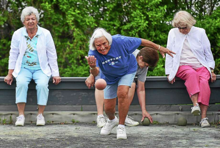 Carol Novella, 83, of East Haven lets the ball go as she plays a friendly game of bocce with, rear from left, Marion Wilson,  81, of Branford, Patricia Gagne, 68, of East Haven, and Dolores Schierholz, 85, of East Haven, at their weekly gathering at the town beach bocce court Thursday. The four play regularly with approximately 8 other female friends. Photo: Peter Hvizdak — New Haven Register  / ©2015 Peter Hvizdak