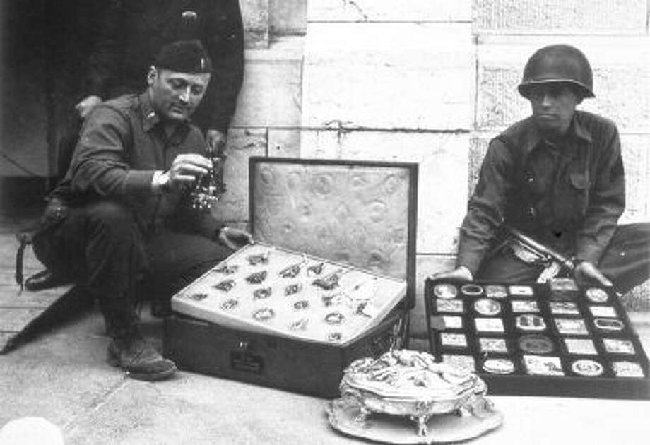 This photo provided by The Monuments Men Foundation for the Preservation of Art of Dallas, shows Monuments Man James Rorimer, left, and Sgt. Antonio Valim examining valuable art objects at Neuschwanstein Castle in Germany which were stolen from the Rothschild collection in France by the ERR and found in the castle in May of 1945.