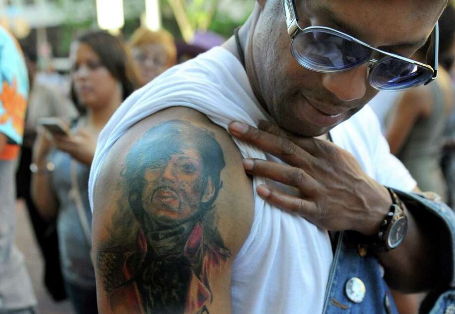 Longtime fan Luther Washington, stationed at Ft Meade, shows off his Prince tattoo while waiting for the doors to open for Prince's Baltimore concert Sunday, May 10, 2015. (Jerry Jackson/The Baltimore Sun via AP) Photo: AP / The Baltimore Sun