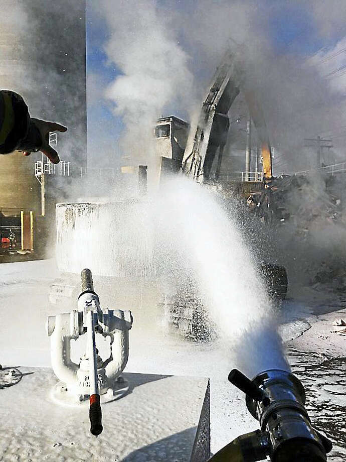Photo courtesy of the New Haven Fire Department New Haven firefighters battled a fire in a piece of excavation equipment Monday night at the Port of New Haven on Waterfront Street. A firefighter suffered a minor neck injury in the blaze Photo: Journal Register Co.