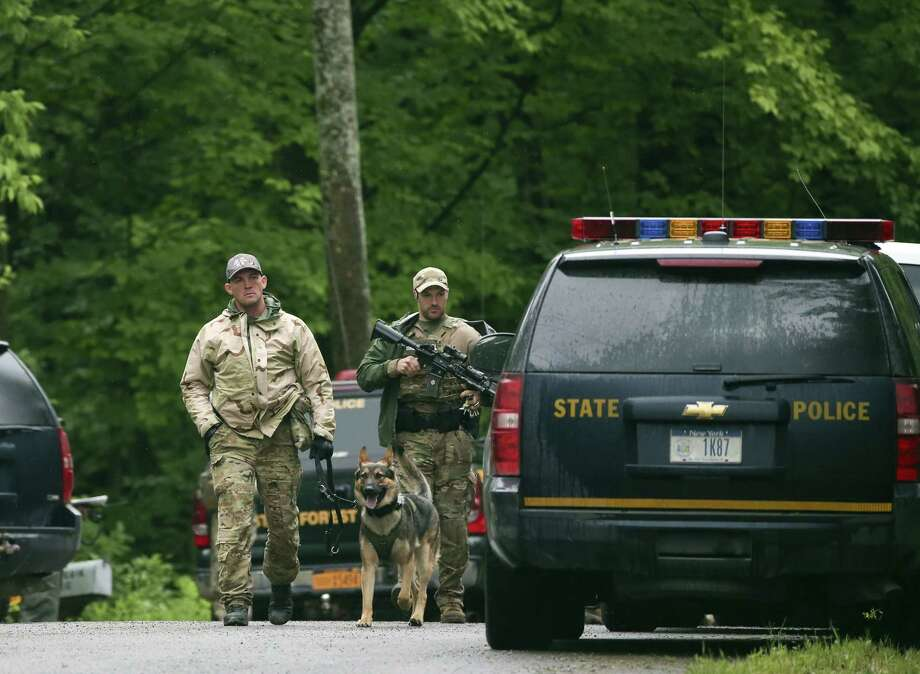 Law enforcement officers walk along a road on Sunday, June 28, 2015, in Malone, N.Y. The shooting death of one escaped killer brought new energy to the three-week hunt for a second escaped murderer in the United States as helicopters, search dogs and hundreds of law enforcement officers converged on a wooded area 30 miles from Clinton Correctional Facility. (AP Photo/Mike Groll) Photo: AP / AP