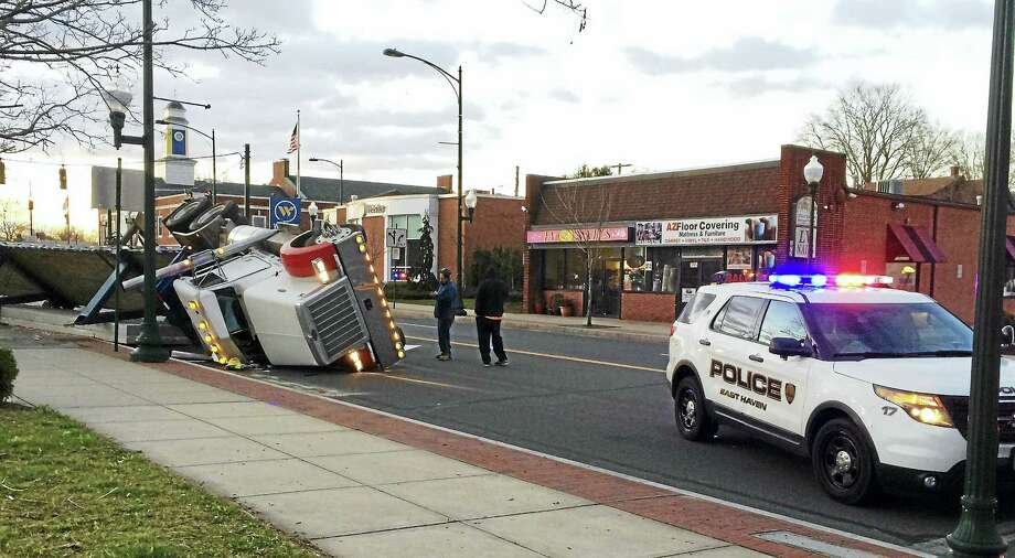Wes Duplantier/New Haven Register Part of Main Street in East Haven was shut down for hours Tuesday morning after a tractor-trailer rolled over and spilled a load of concrete slabs onto the street and sidewalk. The driver suffered only minor injuries, police confirmed. Photo: Journal Register Co.