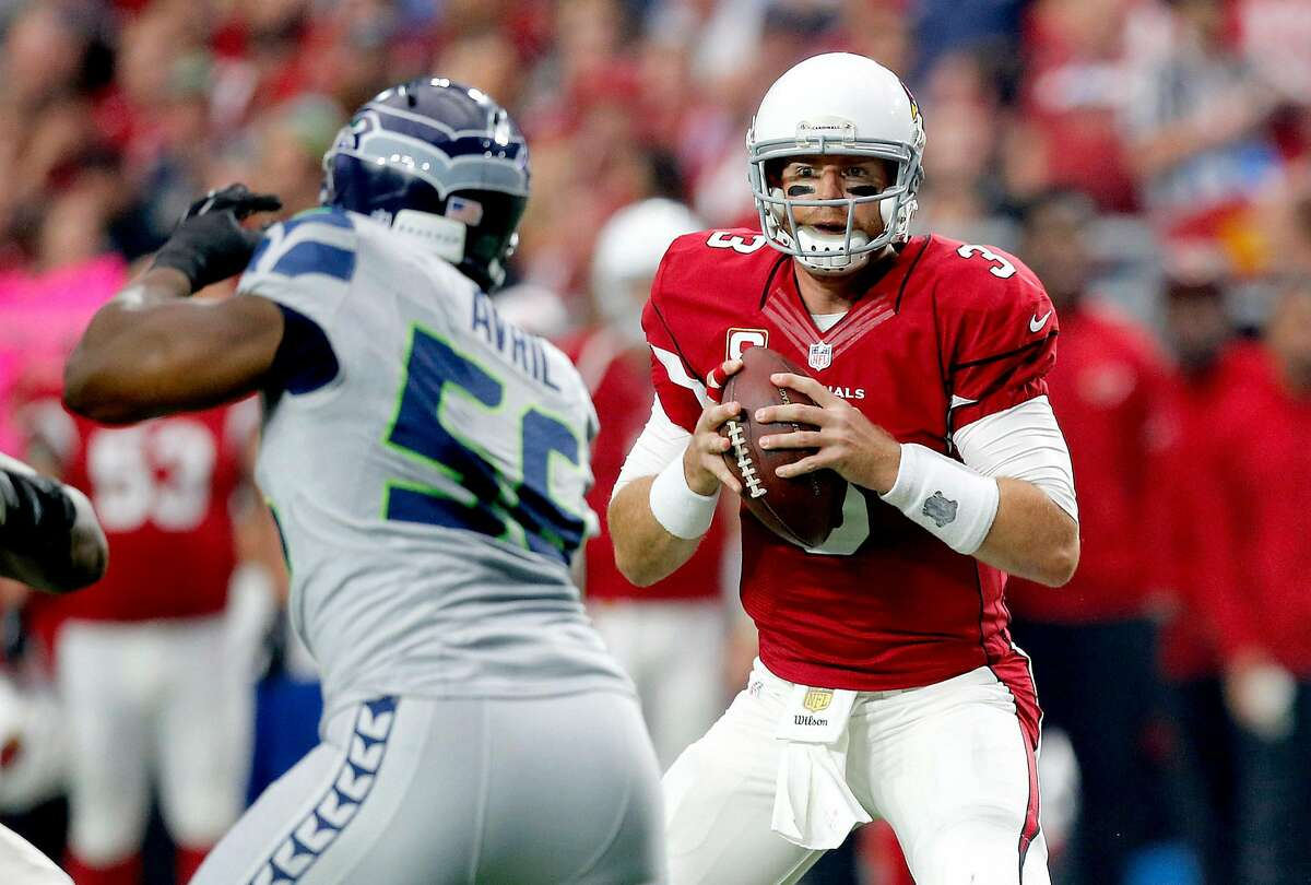 Arizona Cardinals quarterback Carson Palmer (3) eyes Seattle Seahawks defensive end Cliff Avril (56) during the first half of an NFL football game, Sunday, Jan. 3, 2016, in Glendale, Ariz. (AP Photo/Ross D. Franklin)